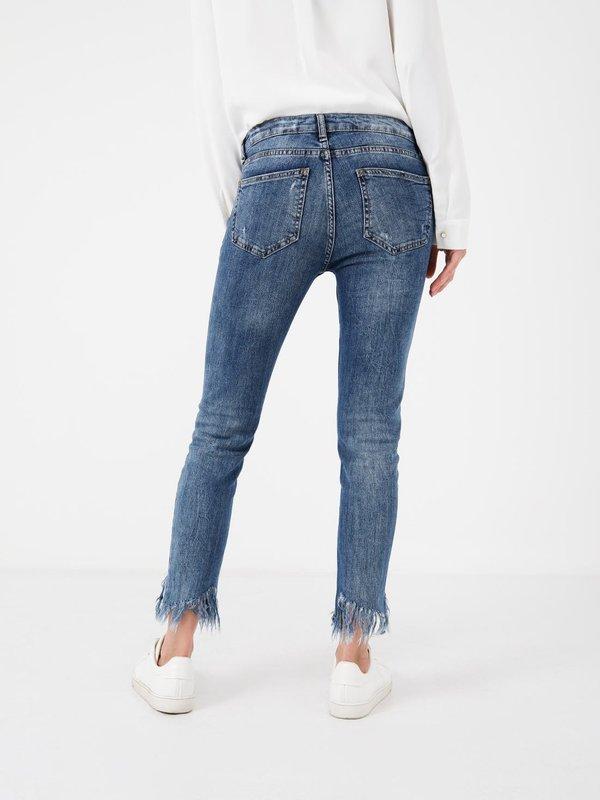 Узкие джинсы с необработанной кромкой по низу вид сзади